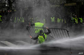 "Anti-riot police use a water cannon during clashes with ""yellow vest"" (Gilet Jaune) protesters during a demonstration on Nov. 30, 2018, near major EU buildings in Brussels."