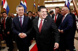 Argentina's President Mauricio Macri, left, and his Paraguay's President Horacio Cartes, arrive for an official meeting at the Conmebol Museum in Luque, Paraguay, March 16, 2017.