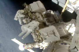 Astronauts Nick Hague and Christina Koch float outside the International Space Station, March 29, 2019, a week after the first spacewalk to install new and stronger batteries for the station's solar power grid.