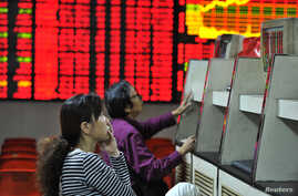 Investors look at computer screens in front of an electronic board showing stock information at a brokerage house in Hefei, Anhui province. Oct. 8, 2013.