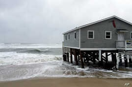 Waves wash ashore hitting a house as winds and storm surge from Tropical Storm Maria lash North Carolinas Outer Banks as the storm moves by well off-shore on Wednesday, Sept. 27, 2017. Dare County officials said the high tide flooded some roads in th