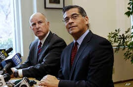 Gov. Jerry Brown, left, and Rep. Xavier Becerra, D-Calif., the governor's nominee for state attorney general, listen to a reporter's questions in Sacramento, Calif. California and other states are weighing legal fights against some of Donald Trump's
