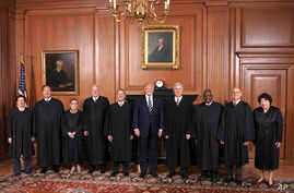 In this image provided by the Supreme Court, President Donald Trump poses with members of the Supreme Court, June 15, 2017, at the court in Washington.