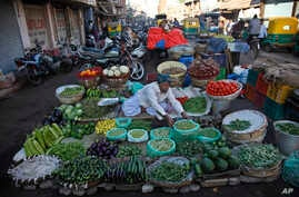 A roadside vendor arranges vegetables at his shop early in the morning in Ahmadabad, India, Dec. 29, 2015.
