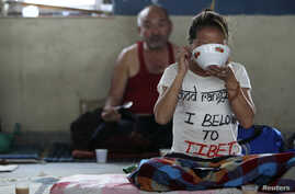 A Tibetan protester eats after the conclusion of a 24-hour hunger strike was held to express solidarity with compatriots who were victims of a Chinese crackdown in Ngaba, Sichuan Province in March, at the Tibetan Youth Club in Katmandu, Nepal, April