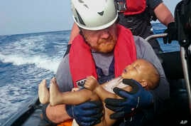 In this Friday, May 27, 2016 photo, a Sea-Watch humanitarian organization crew member holds a drowned migrant baby, during a rescue operation off the coasts of Libya.