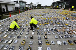 Colombian anti-narcotics policemen inspect packs of cocaine at the police base in Necocli, Feb. 24, 2015.