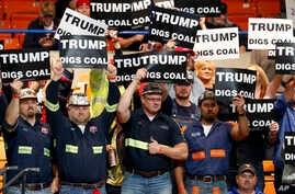 A group of coal miners wave Trump signs as they wait for a rally in Charleston, W.Va., May 5, 2016.
