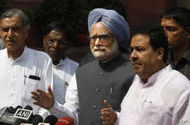 Indian Prime Minister Manmohan Singh, center, talks to the media in New Delhi, Aug. 8, 2012.
