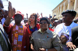 FILE - Morgan Tsvangirai, left, leader of Zimbabwe's main opposition Movement For Democratic Change (MDC), gestures next to Zimbabwe People First (ZIMPF) leader Joice Mujuru, center, who is a former Vice President of Zimbabwe, during a march against