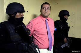 Congressman Julio Juarez Ramirez, who is accused of plotting the murders of two journalists in 2015, is escorted by police officers to court in Guatemala City, Guatemala, Jan. 13, 2018.