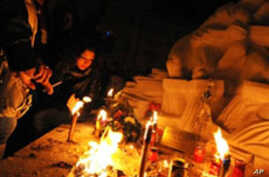People pray near a statue in honor of quake victims during a candle rally in L'Aquila on 06 Apr, 2010, to commemorate the first anniversary of the major earthquake which struck the area