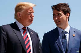 FILE - President Donald Trump talks with Canadian Prime Minister Justin Trudeau during a G-7 Summit welcome ceremony.