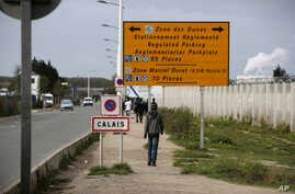 France Migrants Smuggling: FILE - In this Monday, Sept. 26, 2016 file photo, a migrant walks outside the makeshift camp in Calais, northern France. French authorities have arrested and convicted a top smuggler and his accomplice who had reigned over