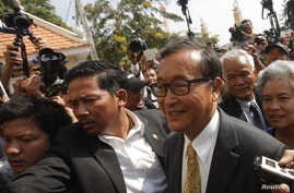 Sam Rainsy (R), leader of the opposition Cambodia National Rescue Party (CNRP), arrives at the Municipal Court in central Phnom Penh, Jan. 14, 2014.