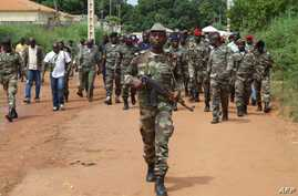 Guinea Bissau soldiers walk on October 21, 2012 in a street of Bissau after gunmen raided a Guinea-Bissau army barracks in the capital, sparking a firefight that left at least seven people dead in the latest unrest to blight the chronically unstable