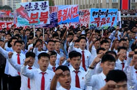 "North Koreans gather at Kim Il Sung Square for a mass rally against America, Sept. 23, 2017, in Pyongyang, North Korea, a day after the country's leader issued a rare statement attacking Donald Trump. The sign on the left reads ""decisive revenge"" and"
