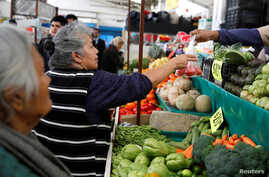A woman buys tomatoes in a groceries stall at Granada market in Mexico City, Mexico, Jan. 10, 2017.