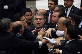 FILE - Ruling Justice and Development Party lawmakers, right, and members of the opposition Republican People's Party skirmish in parliament during debate on corruption charges against ministers in the cabinet of then-Prime Minister Recep Tayyip Erdo