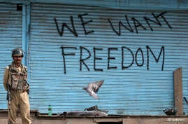 FILE - Graffiti is painted on shop shutters in Srinagar after an escalation of violence that officials have blamed on separatist protests that have tied down security forces for more than a month in Kashmir, Aug. 17, 2016.