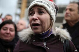 A woman reacts as police officers carry the coffin of police officer Fethi Sekin, who was killed in a car bomb attack, during his funeral in the Aegean city of Izmir, Turkey, Jan. 6, 2017.