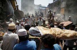 The body of a victim is carried out from the site of a building collapse in Mumbai, India, Aug. 31, 2017. A five-story building collapsed Thursday in Mumbai, Indian's financial capital, after torrential rains lashed western India.