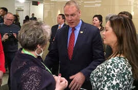Newly sworn-in Interior Secretary Ryan Zinke, and his wife Lola, right, greets an Interior Department employee on the Interior Department's 168th birthday, March 3, 2017, at the Interior Department in Washington.