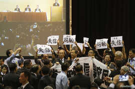 Pro-democracy lawmakers hold up a banner and signs during a protest as Li Fei (seen on screen), deputy general secretary of the National People's Congress (NPC) standing committee, speaks during a briefing session in Hong Kong, September 1, 2014.