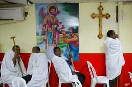 FILE -  Eritrean Christian Orthodox migrants attend a mass at a makeshift church in Tel Aviv, Israel, May 7, 2016.