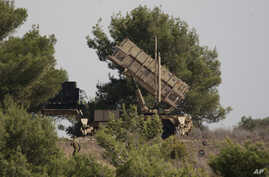 FILE - An Israel soldier walks past a Patriot missile defense battery positioned on the Carmel Mount, Israel, Oct. 9, 2012.