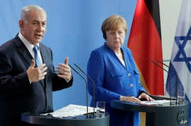 German Chancellor Angela Merkel, right, and Israel's Prime Minister Benjamin Netanyahu, left, address the media during a joint press conference as part of a meeting at the Chancellery in Berlin, Germany, Monday, June 4, 2018.