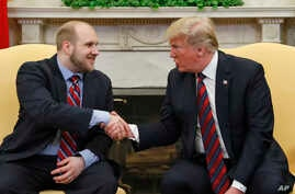 President Donald Trump shakes hands with Joshua Holt, who was recently released from a prison in Venezuela, in the Oval Office of the White House, May 26, 2018, in Washington.