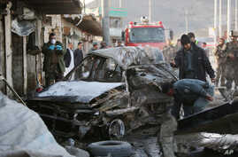 Afghan security personnel gather at the site of a suicide attack in Kabul, Afghanistan, April, 10, 2015.