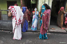 Indian sex workers cover their faces as they react to the camera while watching a rally as part of the week-long sex workers' freedom festival at the Sonagachi red-light area in Kolkata July 24, 2012.Indian sex workers cover their faces as they react