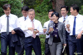 South Korean President Moon Jae-in takes a walk with senior presidential secretaries at the Presidential Blue House in Seoul, South Korea, May 11, 2017.