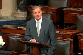 In this image from Senate Television, Sen. Lindsey Graham, R-S.C., speaks on the Senate floor at the Capitol in Washington, Aug. 28, 2018, next to the desk of Sen. John McCain, R-Ariz., draped in black with a bowl of white roses sitting on it.