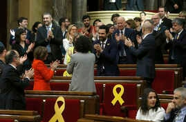 Deputy Roger Torrent, center, is congratulated after being elected as the new president of the Catalan parliament after a parliamentary session where elected lawmakers meet for the first time after regional elections in Catalonia, Barcelona, Spain, J
