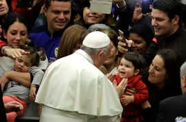 """Pope Francis is cheered by faithful as he arrives for a special audience granted to some of the employees of the """"Bambin Gesu """"pediatric hospital in the Paul VI hall, at the Vatican, Thursday, Dec. 15, 2016."""