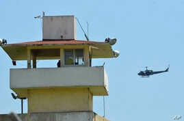 A police helicopter flies over the state prison in Acapulco, Mexico, July 6, 2017. Fighting erupted between rival gangs inside the prison before dawn Thursday.