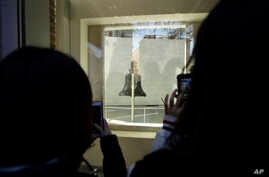 Tourists to Independence National Historical Park take photographs through a window of the closed building housing the Liberty Bell, Wednesday, Dec. 26, 2018, in Philadelphia. The building is closed due to the partial government shutdown.