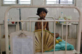 FILE - A girl, who fell sick after consuming contaminated meals given to children at a school on Tuesday, rests inside a hospital in the eastern Indian city of Patna, July 18, 2013.