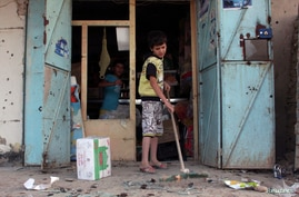 An Iraqi boy cleans up the site of a bomb attack in Husseiniya district in Baghdad, July 31, 2013.