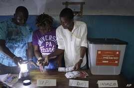 Election workers count presidential ballots by lamplight at a polling station in the West Point neighborhood of Monrovia, Liberia Tuesday, Nov. 8, 2011