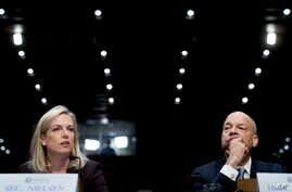 Homeland Security Secretary Kirstjen Nielsen, left, accompanied by former Homeland Security Secretary Jeh Johnson, right, testifies at a Senate Intelligence Committee hearing on election security on Capitol Hill in Washington, March 21, 2018.