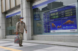 A man walks past an electronic stock indicator of a securities firm in Tokyo, Wednesday, Jan. 6, 2016.