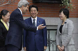 Secretary of State John Kerry, second from left, greets Japanese Prime Minister Shinzo Abe, center, and his wife Akie Abe, right, in front of Kerry's residence in the Beacon Hill neighborhood of Boston, Sunday, April 26, 2015.