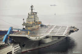 FILE - China's first aircraft carrier, which was renovated from an old aircraft carrier that China bought from Ukraine in 1998, is seen docked at Dalian Port, in Dalian, Liaoning province September 22, 2012.
