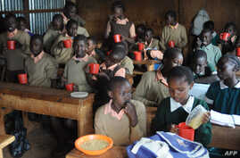 Pupils at the Stara primary school in Nairobi's Kibera slum eat a meal provided by the World Food Program (WFP), May 26, 2009, as part of a school feeding program.