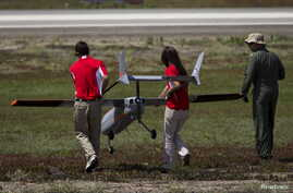 The FireFlight UAS TwinHawk is carried to the runway during Black Dart, a demonstration of 55 unmanned aerial vehicles, or drones, at Naval Base Ventura County Sea Range, Point Mugu, near Oxnard, Calif., July 31, 2015.