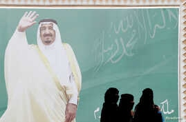 FILE - Women walk past a poster of Saudi Arabia's King Salman bin Abdulaziz Al Saud during Janadriyah Cultural Festival on the outskirts of Riyadh, Saudi Arabia Feb. 12, 2018.
